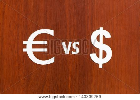 Paper currency signs Euro VS Dollar. Abstract conceptual image. Wooden background