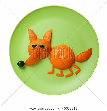 Funny fox made of orange on green plate