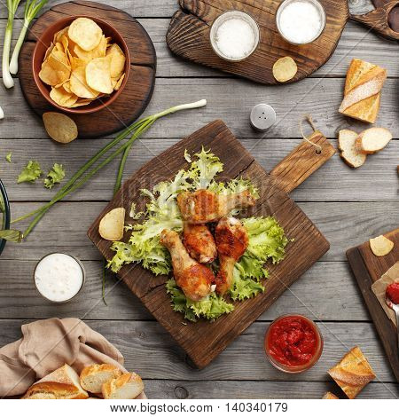 Fried chicken legs with sauce chips and lager on wooden table top view. Outdoors Food Concept