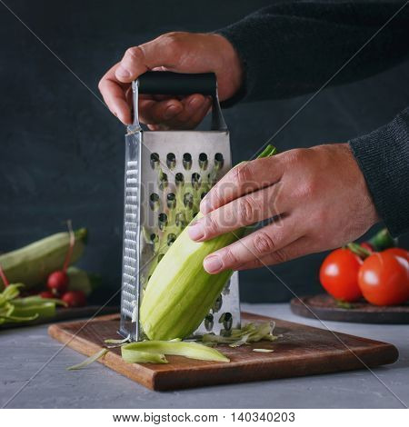 Man preparing vegetarian healthy food from the vegetable marrows in the kitchen