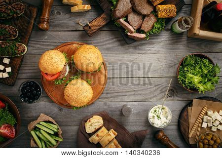 Different food on a wooden table burgers steak eggplant with meat vegetables salad and variety of snacks on wooden table with copy space top view. Outdoors food Concept