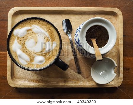 Hot coffee in black cup and brown sugar in earthenware for wooden tray.