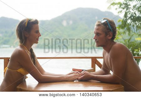 Cute couple wearing swimwear in love holding hands and smiling sitting at the table in cozy summer cafe on the beach