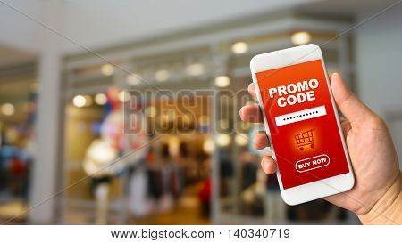 Woman hand holding smartphone against blur bokeh of shop background with word promo code buy now
