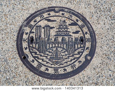OSAKA, JAPAN - JUNE 09, 2016: A manhole cover in Osaka, Japan. A ship on Dotonbori canal and Osaka castle engraved on to a manhole cover as a symbol of an important city's landmark.