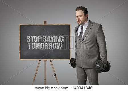 Stop saying tomorrow  text on blackboard with businesssman holding weights