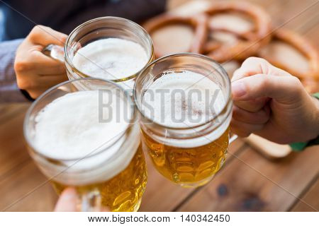 people, leisure and drinks concept - close up of male hands clinking beer mugs at bar or pub