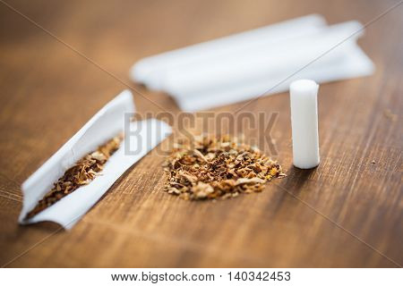 drug use, substance abuse, nicotine addiction and smoking concept - close up of marijuana or tobacco with cigarette paper and filter
