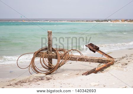 Old large anchor lying on the beach