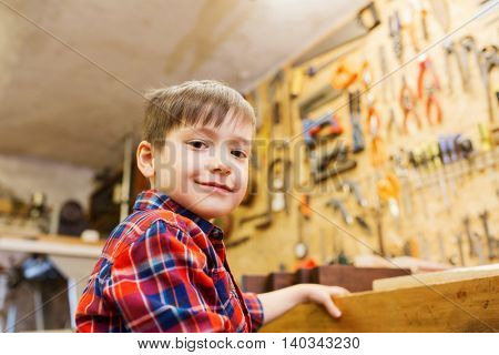 children, profession, carpentry, woodwork and people concept - happy little boy with wood plank at workshop
