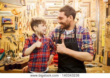 family, carpentry, woodwork, gesture and people concept - happy father and little son making thumbs up at workshop