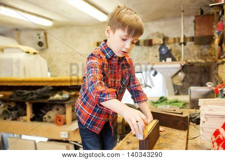children, profession, carpentry, woodwork and people concept - happy little boy with ruler measuring wood plank at workshop