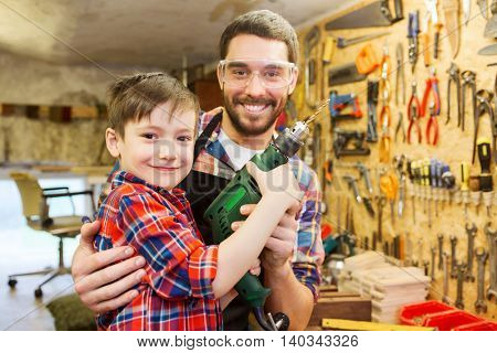 family, carpentry, woodwork and people concept - happy father and little son with drill working at workshop
