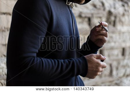 drug use, substance abuse, addiction, people and smoking concept - close up of addict hands with marijuana joint and lighter