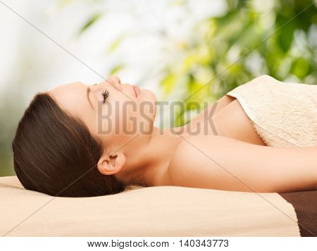 beauty and spa concept - woman in spa lying on the massage desk