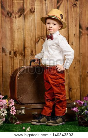 Little gentleman in elegant clothes is going to trip with his old suitcase. Kid's fashion. Childhood. Summer holidays. Retro style.