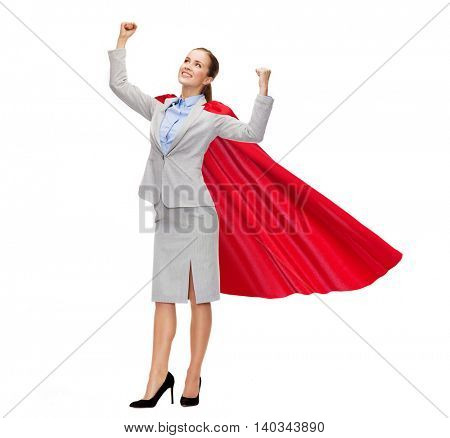 business, power, success, achievement and people concept - young smiling businesswoman in red superhero cape holding raised fists