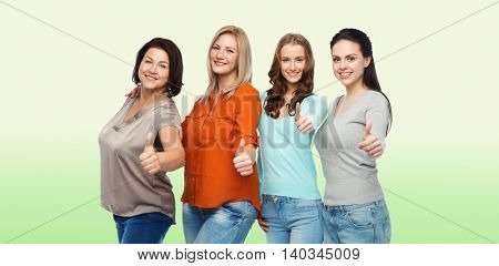 friendship, fashion, body positive, gesture and people concept - group of happy different size women in casual clothes showing thumbs up over green natural background