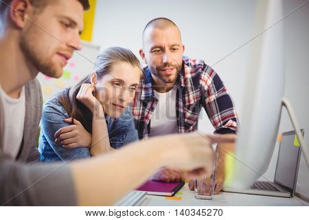 Businessman pointing on computer while discussing with colleagues at desk in creative office