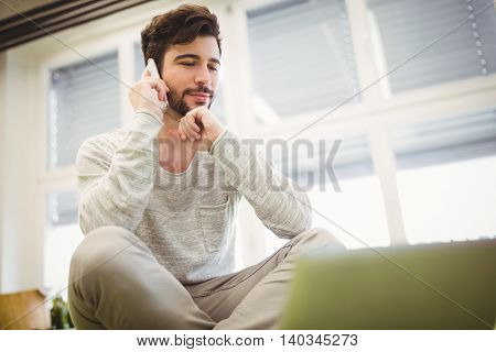 Low angle view of businessman using mobile phone in creative office