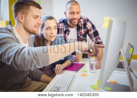 Young businessman pointing on computer while discussing with colleagues at desk in creative office