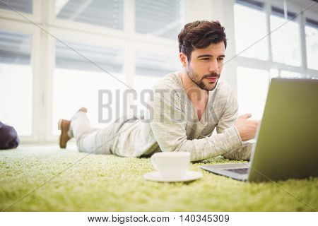 Young businessman lying on carpet while using laptop in creative office