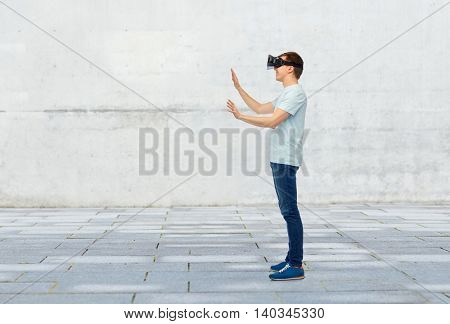 3d technology, virtual reality, entertainment, cyberspace and people concept - happy young man with virtual reality headset or 3d glasses playing game and touching something over street background