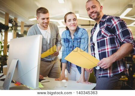 Portrait of smiling business people holding paper at desk in creative office