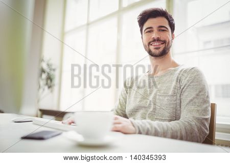 Portrait of confident businessman working at desk in creative office