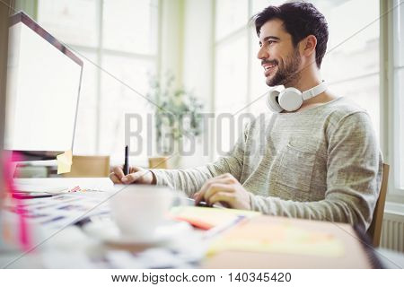 Smiling businessman working on computer in creative office