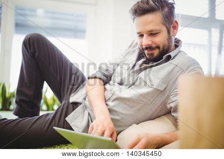 Happy businessman working on laptop in creative office