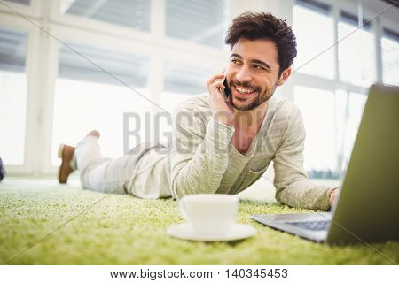 Young businessman talking on mobile phone while lying in creative office