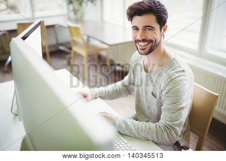 Portrait of smiling businessman working at desk in creative office