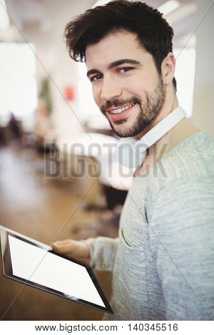 Portrait of young businessman holding digital tablet in creative office