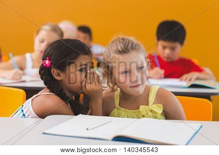 Schoolgirl whispering into her friend s ear in classroom at school