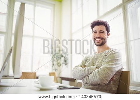 Portrait of smiling businessman sitting at desk in creative office