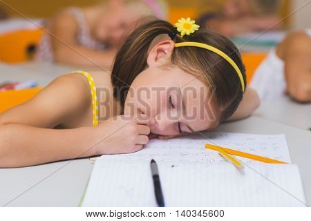 Schoolgirl sleeping at desk in classroom