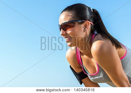 Close up portrait of young athlete with sportive eye wear and smart phone activity armband against blue sky.