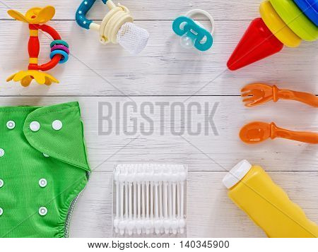 Babies goods: cloth diaper, baby powder, nibbler, teether, soother, cotton swabs, baby spoon and fork, pyramid toy on white wooden background with copy space. Top view or flat lay
