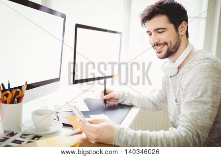 Smiling businessman using graphics tablet at desk in creative office