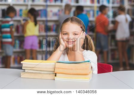 Portrait of girl sitting with pile of books in library at elementary school
