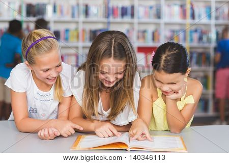 School kids reading book together in library at elementary school