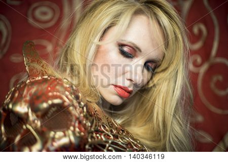Makeup, blonde dressed in red armor gold on red art nouveau flourishes