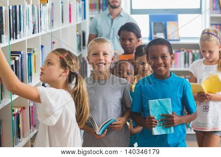 Girl removing book from bookshelf in library at elementary school