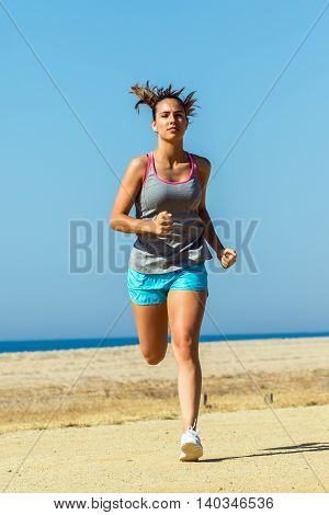 Full length front view action shot of attractive young girl athlete running towards camera.