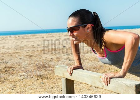 Close up portrait of attractive girl warming up on wooden structure at sea front.