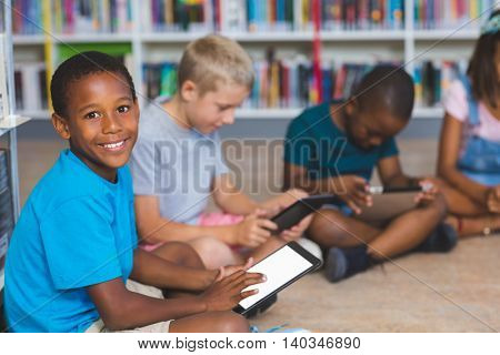 School kids sitting on floor using digital tablet in library at elementary school