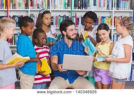 Teacher teaching kids on laptop in library at elementary school