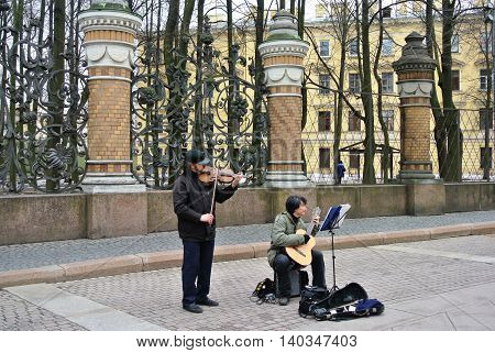 SAINT-PETERSBURG, RUSSIA - APRIL, 2013: Unknown street musicians earn playing musical instruments  on background of lattice of Summer Garden
