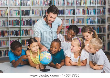 Pupils and teacher looking at globe in library at elementary school